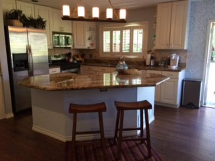 Large granite island, SS appliances, new hardwoods, fully stocked kitchen.