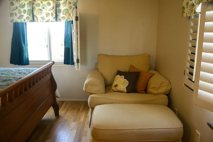 Cozy chair in bedroom. Relax and read a book or catch up on email.