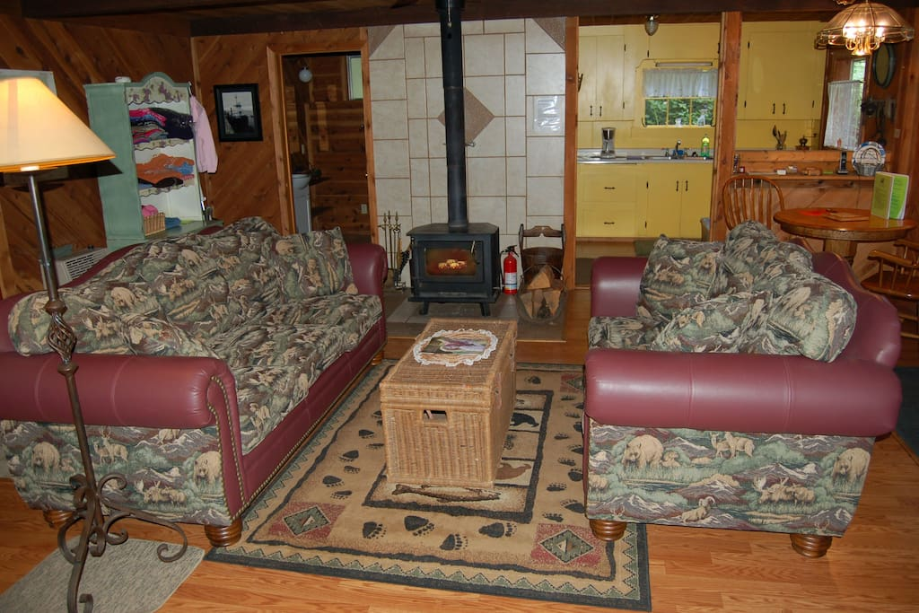 Living room to kitchen. Cozy wood stove. Full bathroom is to left; front door just right of dining set