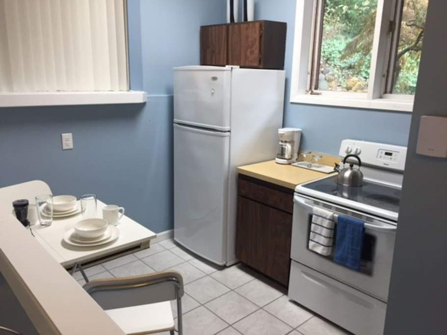 Full kitchen with full sized refrigerator, stove, microwave and sink.