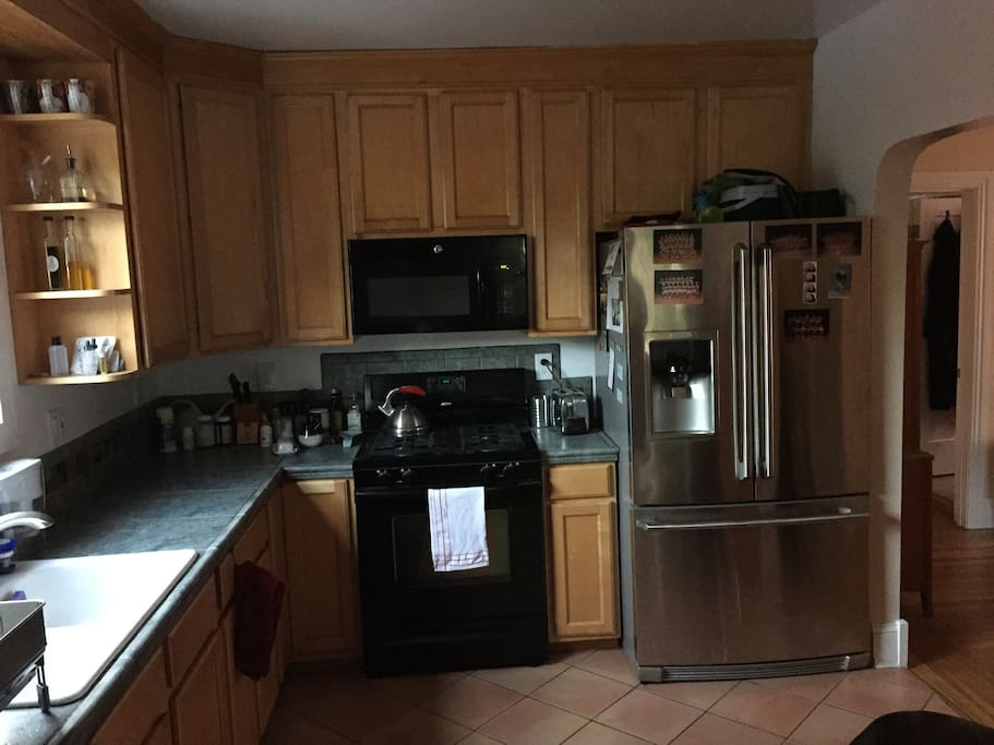 The kitchen with gas stove, big fridge, microwave, dishwasher, toaster oven, a Keurig coffee maker, a Nespresso espresso maker, and a Vitamix blender