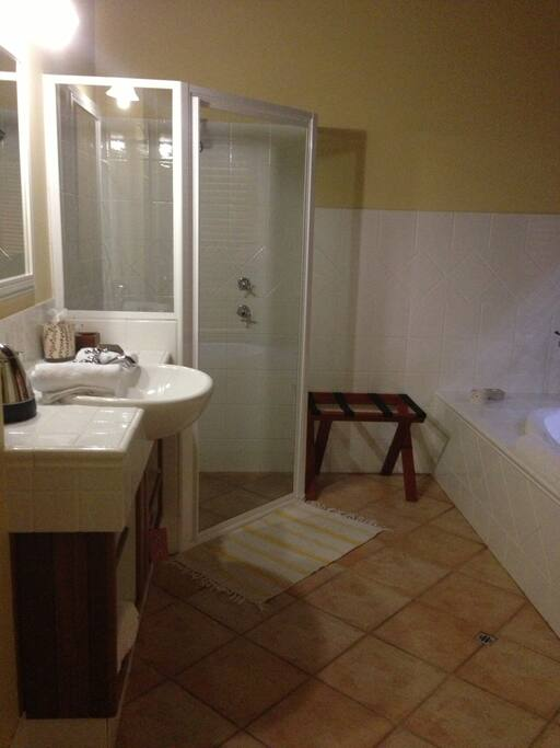 Ensuite bathroom with walk in shower and spa bath with candles...