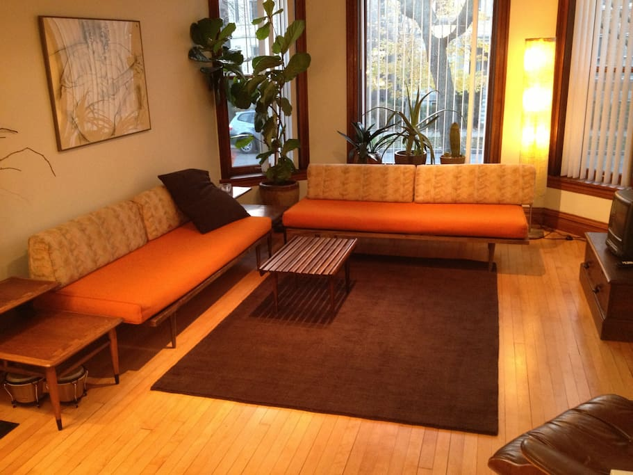 Frontroom with afternoon sun, vintage modern furniture.  Small TV and speaker for iPod.