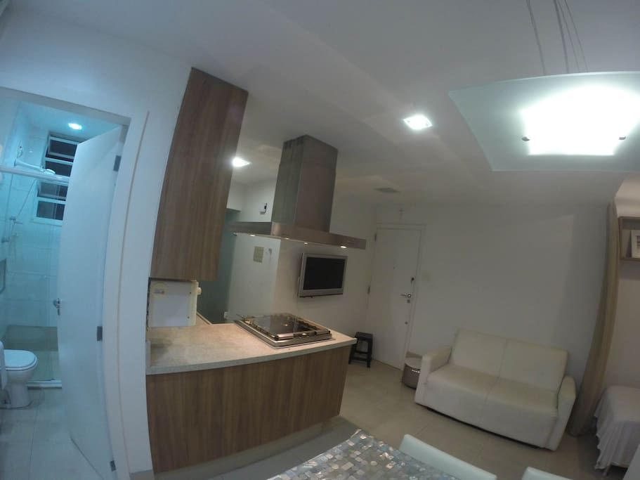 Looking back at the kitchen and TV across the living area, with view of the bathroom to the left
