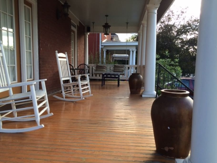 Front porch with swing, rocking chairs, seating, outdoor speakers.