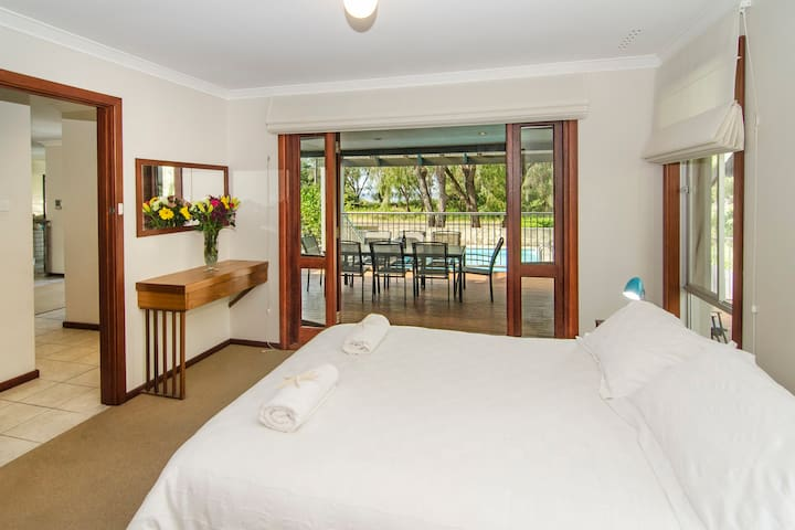 The master queen bedroom with french doors opening onto the front patio that has gorgeous views of the beach.
