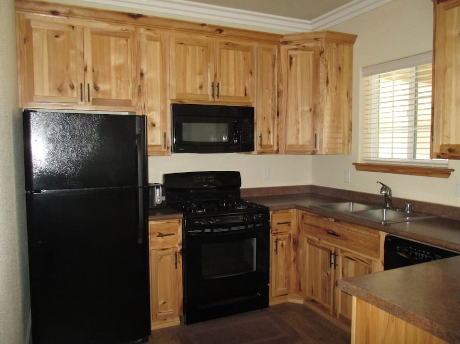 Large kitchen with dishwasher, oven, cooktop, microwave and full size refrigerator.