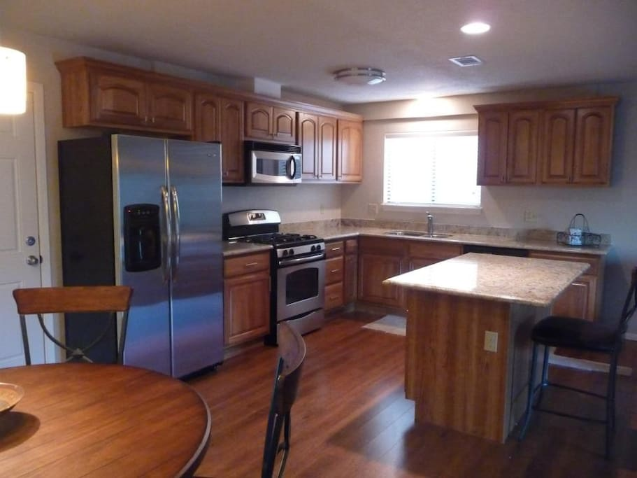 Open kitchen with new appliances and granite countertops