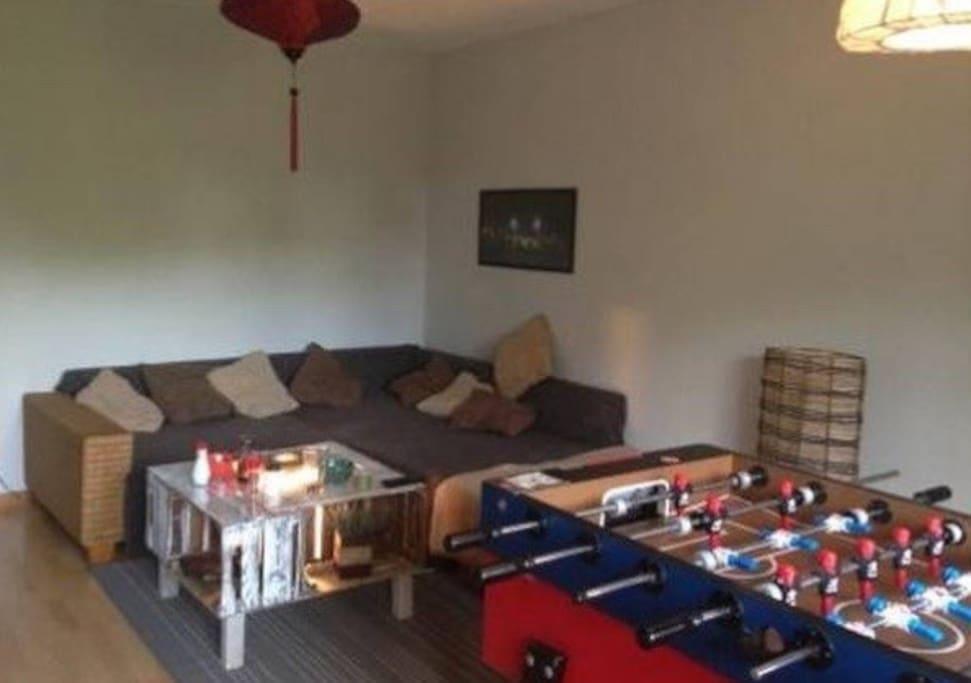 Wohnzimmer mit Couch und Kicker