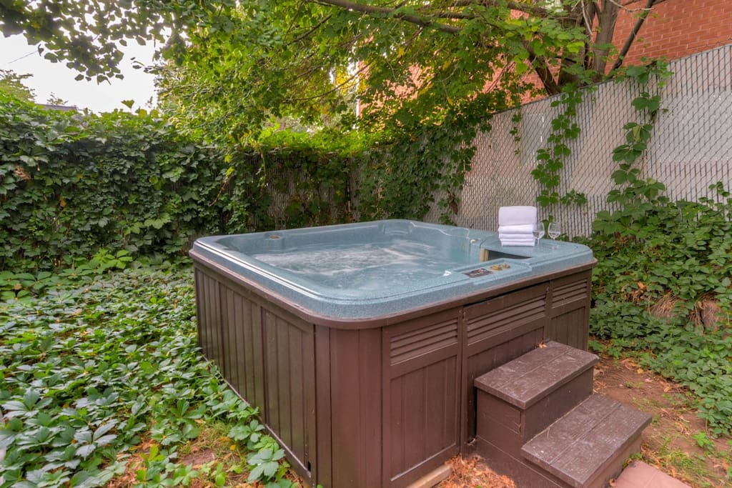 Private hot tub in private backyard courtyard accessed from lower apartment