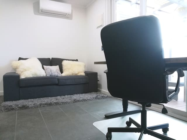 Apartment's comfortable couch and work area in kitchen/dining room, with direct access to downstairs deck and street via lockable gate.