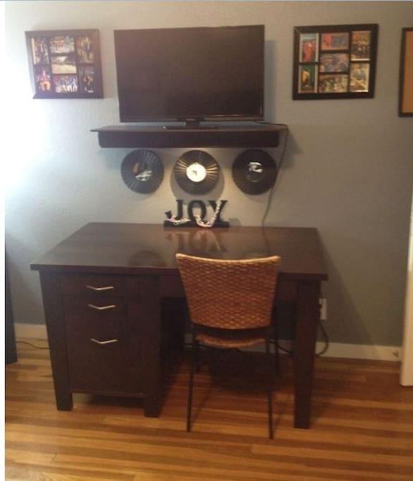 Desk, flatscreen, tv, Apple desktop computer and printer (not shown).