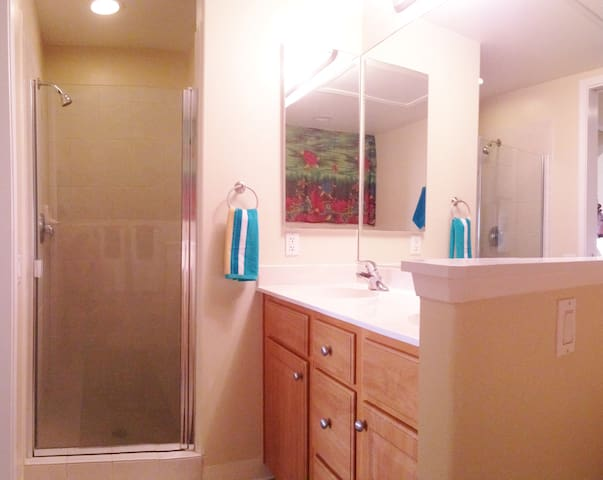 The master bath has a glass and tile shower with a built-in seat and shelving.