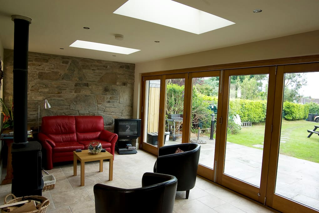 Spacious sunroom with bi-fold doors, log burner, and has a 40 inch flat screen TV and DVD player
