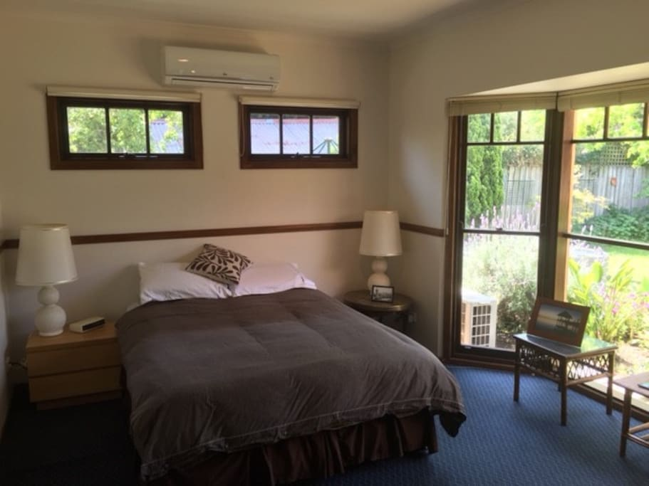 Queen sized bed in large private and secure room overlooking sunny courtyard & garden with air con/heater.