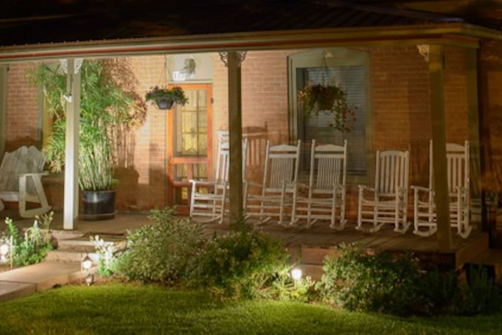 Porches with rocking chairs and porch swings surround the property