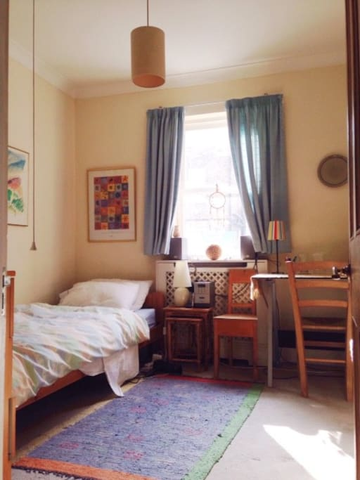 Very quiet room with clothes rack and chest of drawers