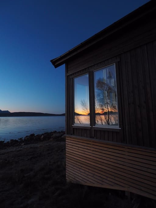 Sunset in October reflected in the windows of the cabin.  Photo by Mario