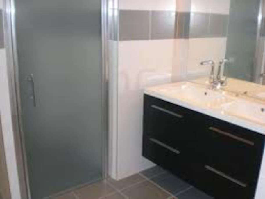 Dans le couloir , Salle de bain moderne avec douche, toilette, et deux éviers.