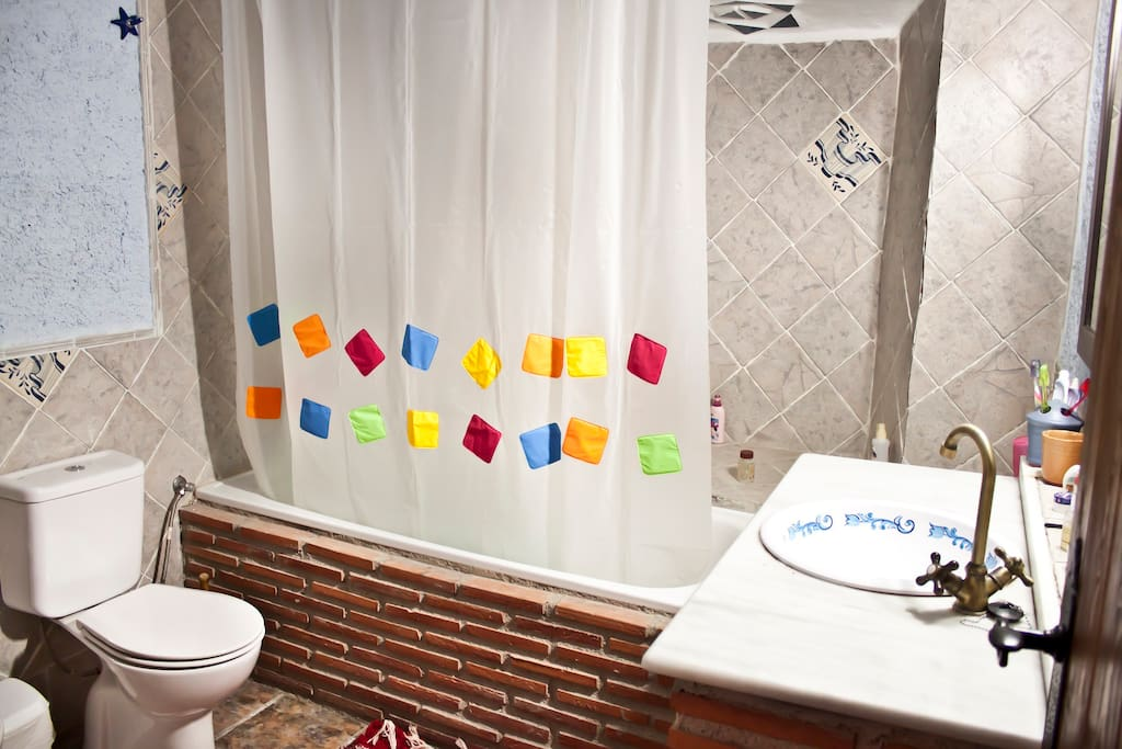 Baño completo con bañera y vigas de madera.