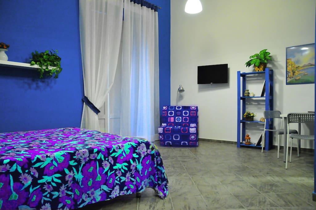 Camera  AZZURRA,   di circa 23 mq. oltre il bagno, molto luminosa con affaccio sulla strada principale. 3 posti letto     n.2 letti singoli o un matrimoniale più uno in poltrona letto.