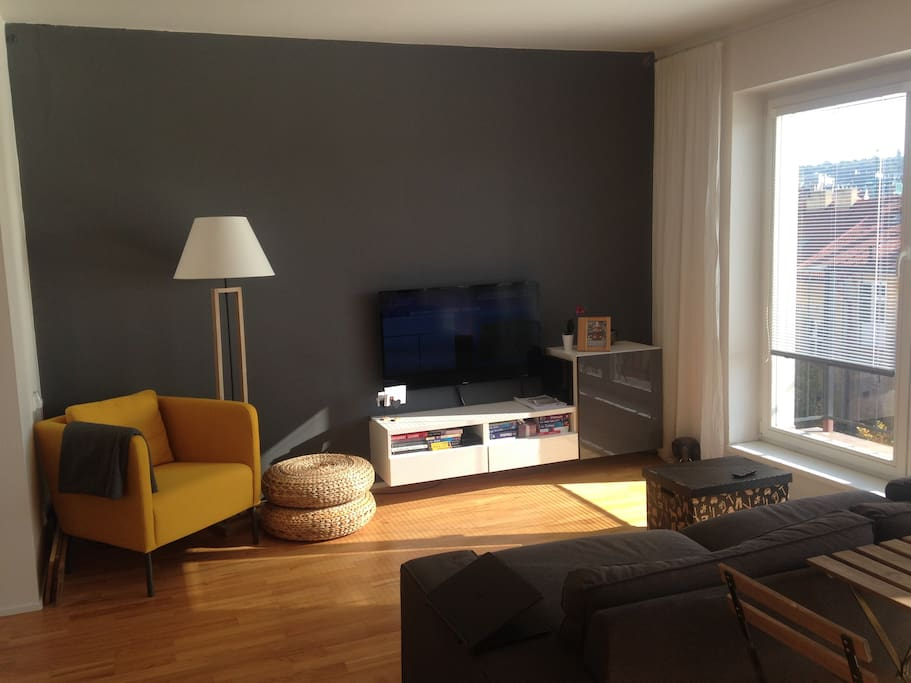 Bright living room with entrance to balcony and large TV