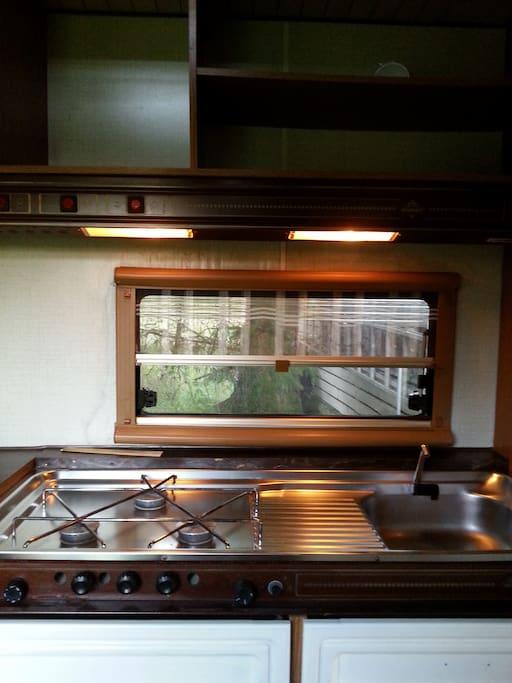Køkken med gasblus og køleskab.