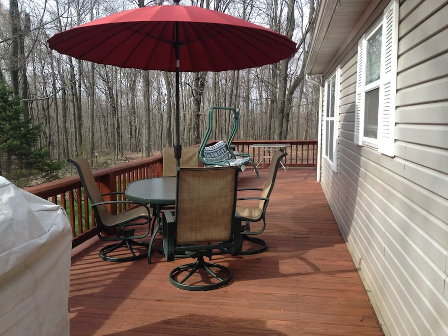 Spacious wrap around deck with multiple seating and gliders,  chairs, fire pit and access to Hot tub!