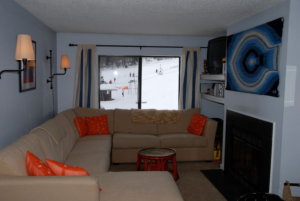 Living room with large sleeper sectional (full) and fireplace.