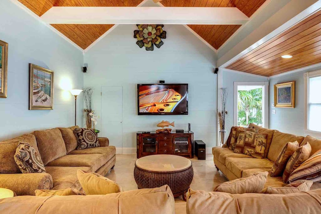 The vaulted living room has three big sofas and a huge flat screen TV...