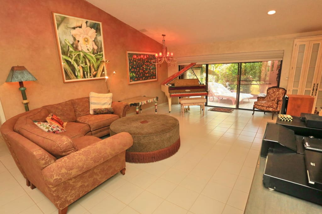 Living room with large screen TV, cable, baby grand piano and comfortable sitting space
