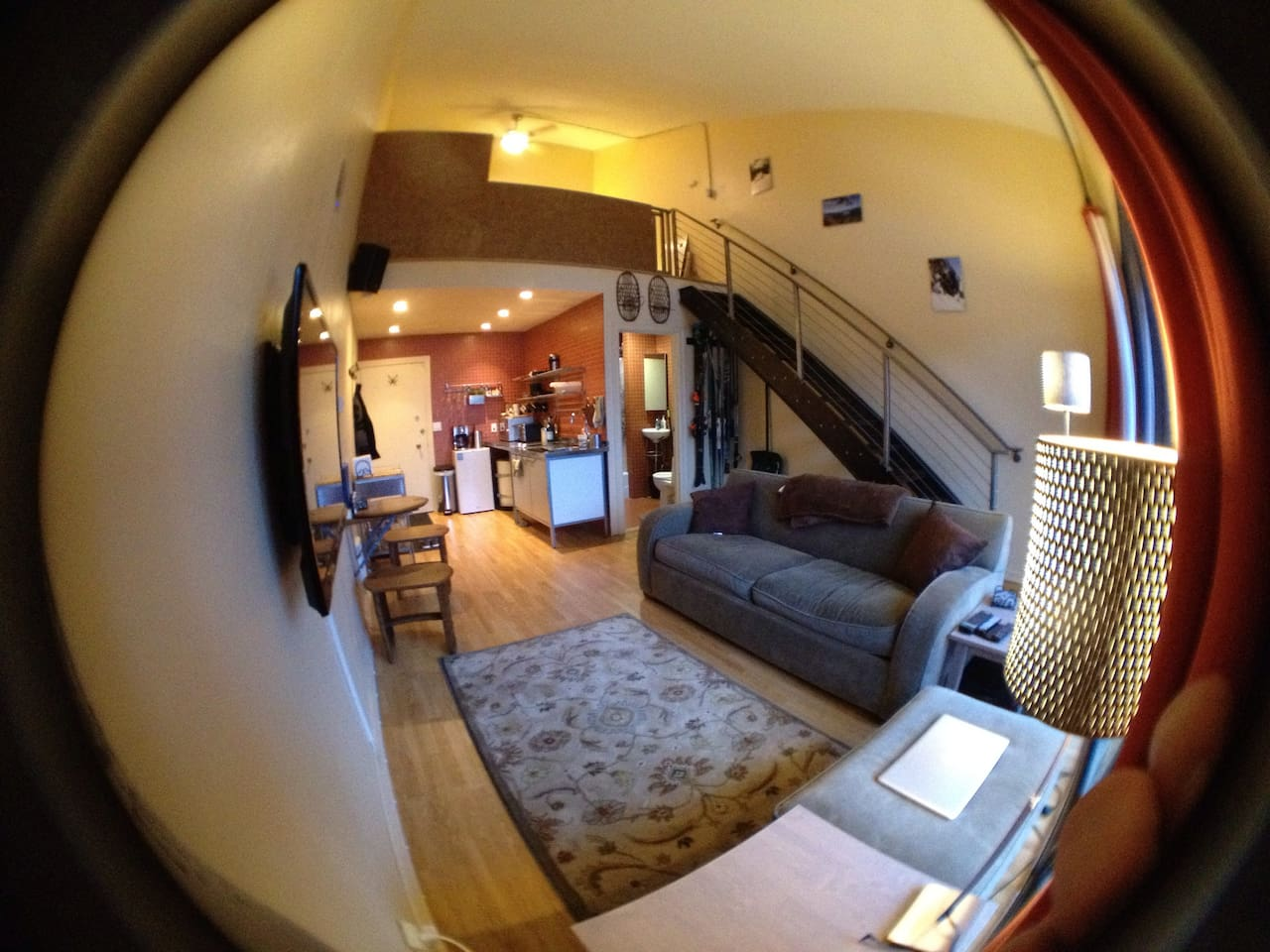 View of entire apartment - living area in foreground, kitchen/bathroom in background.