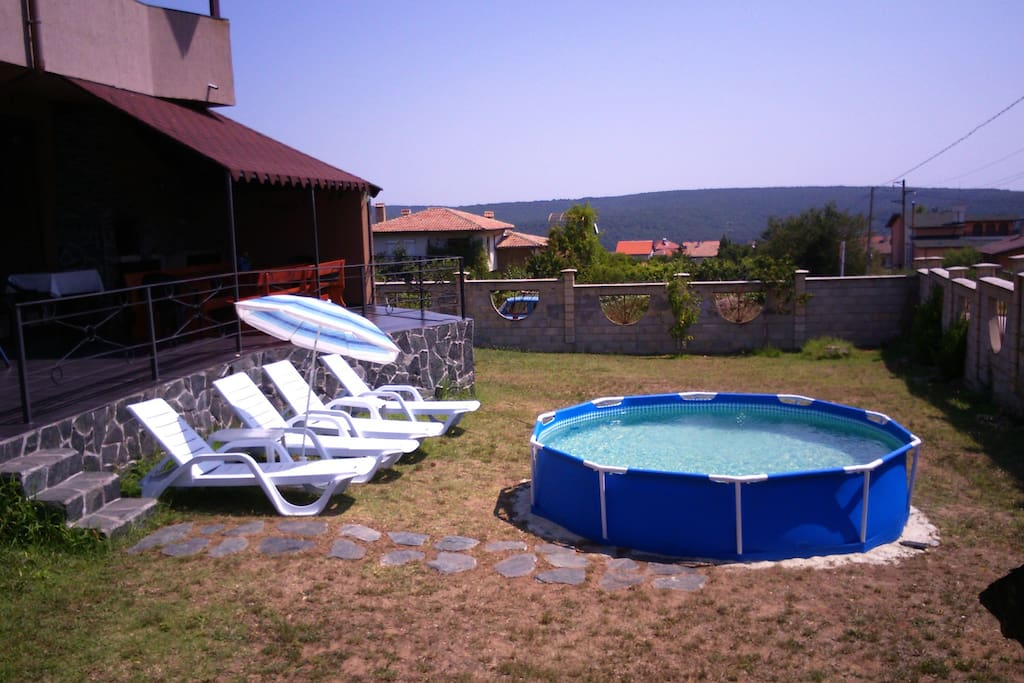 The backyard with the pool and the barbeque in the background