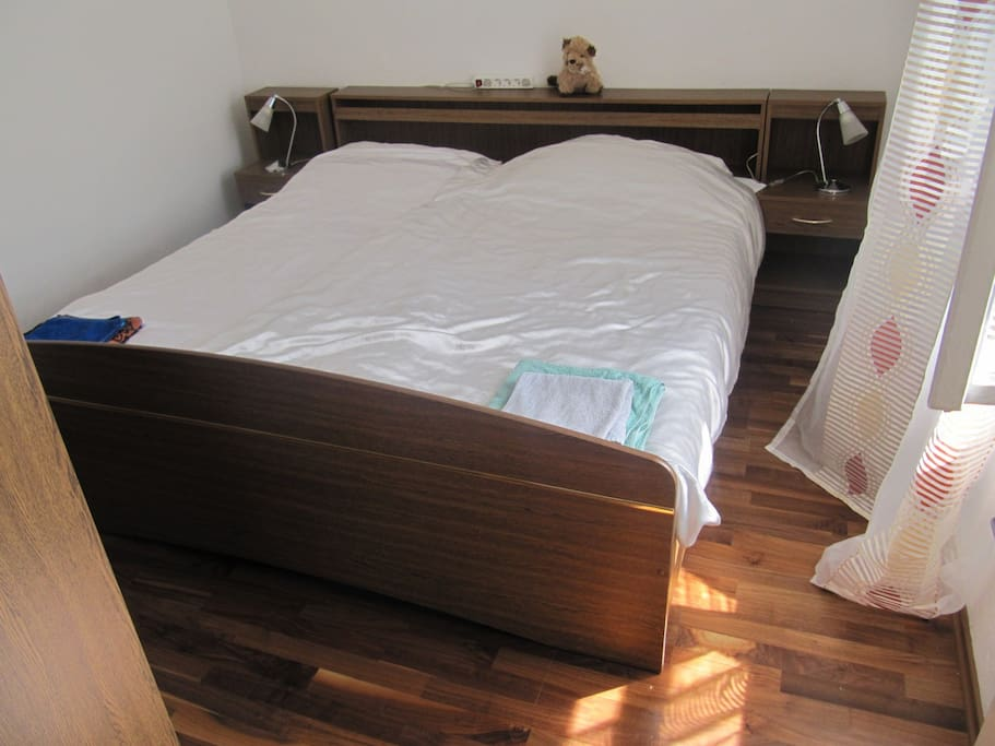 A bedroom for two, with real-wood oak floor and a nice view.