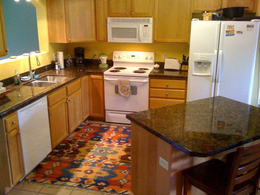 The kitchen with granite countertops, garbage disposal and dishwasher