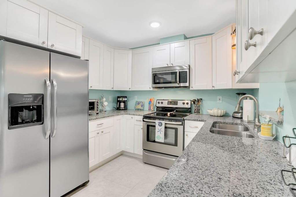 The modern kitchen is configured with stainless steel appliances and granite countertops.