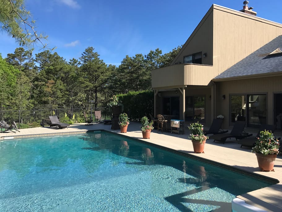 Heated pool with 6 lounge chairs, outdoor bar and eating table in a secluded private backyard