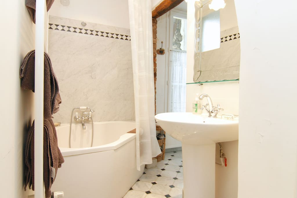 Marbre bathroom equipped with a strong shower and a heater.
