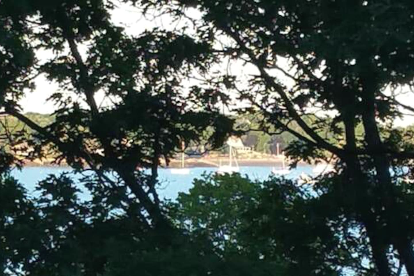 Zoomed in view of peaks from the house/deck through the trees to the harbor from the deck in July ; ).