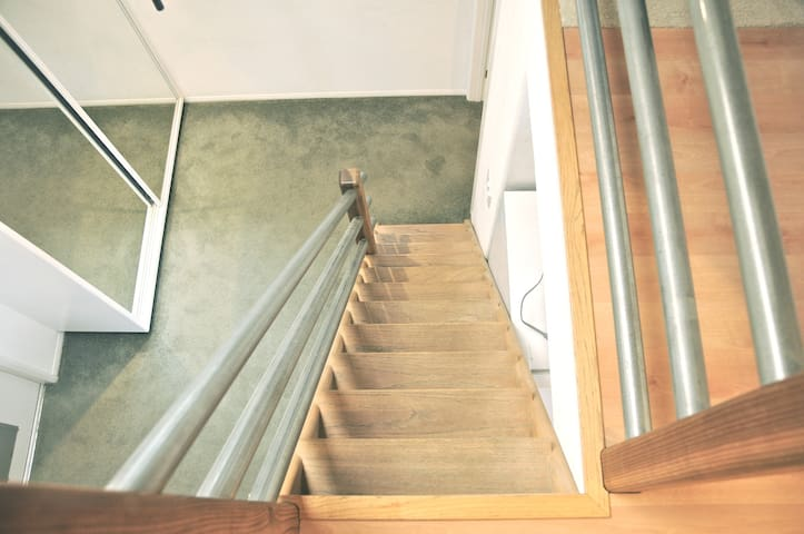 Stairs leading up to open plan bedroom