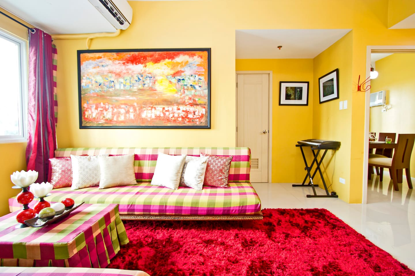 Living Room has A/C, piano, mahogany center table and couches with customized curtains and  fabric. The painting is called Habagat (Typhoon) painted by 3 Marias (Bea, Joy and May) under the supervision of Artist/Master Rolly Rosal.