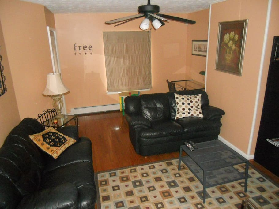 The living room is comfortable and spacious with ample light and leather couches.