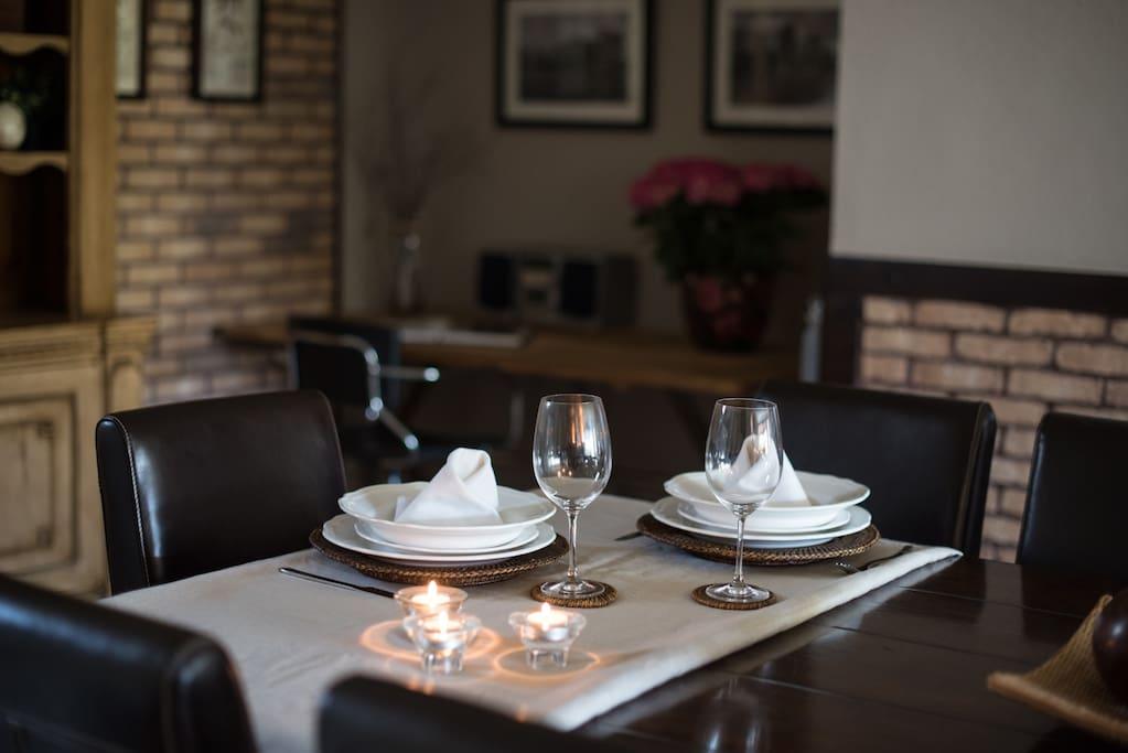 mesa comedor con vajillas, velas, mantel, etc