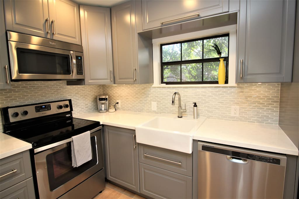 Full-sized glass-topped range, microwave, and dishwasher with apron front sink