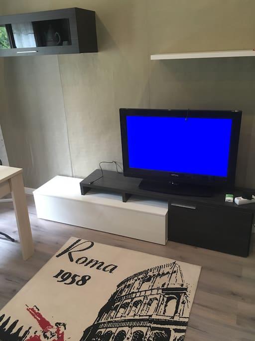 salon con tele, mesa de comedor y sofa