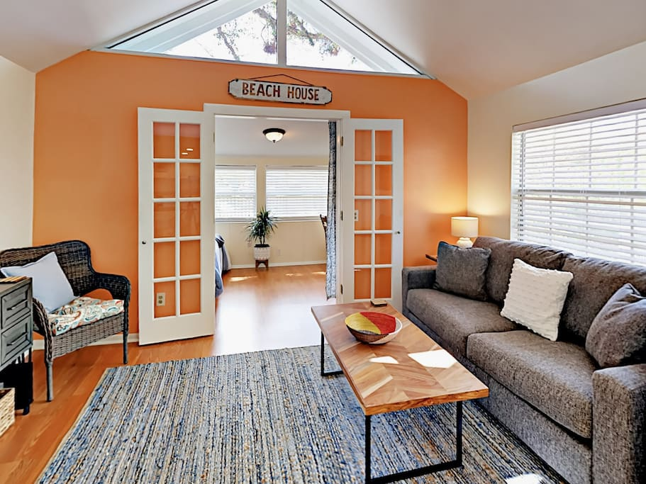 Welcoming living area with seating for 3 and a cheerful color palette.