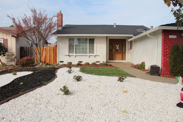 Front of the house features white stones, geranium plants and a mulberry tree.