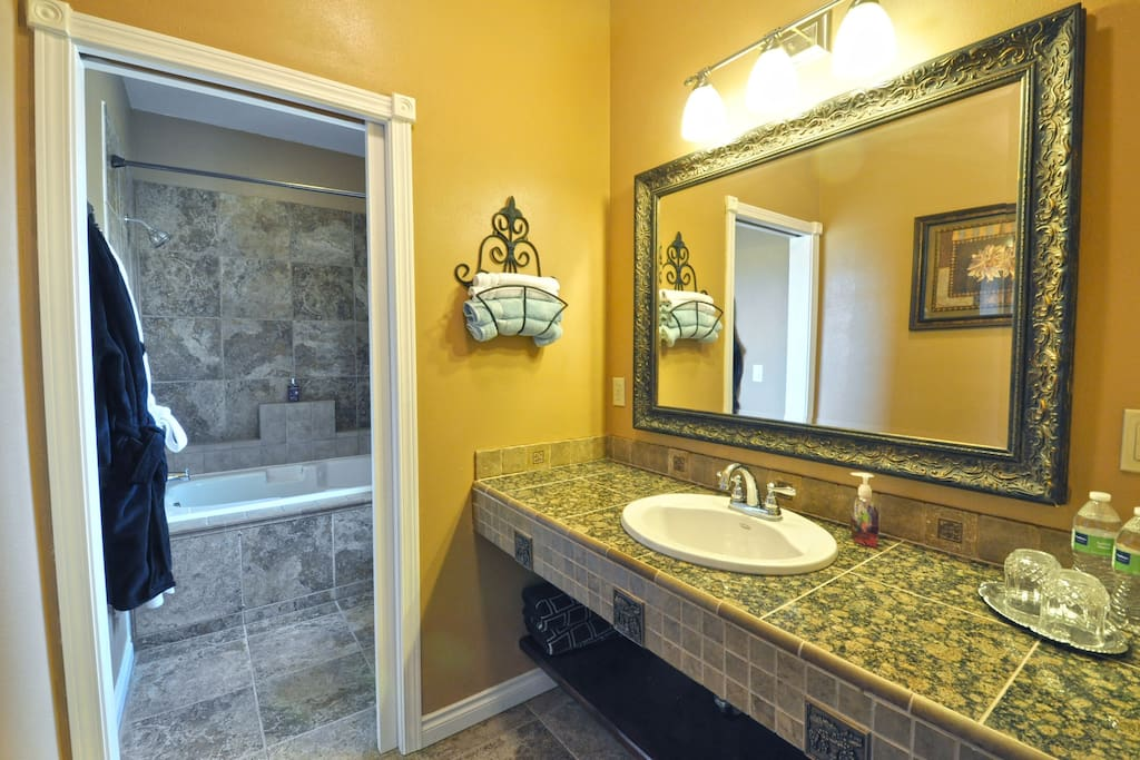 Granite stone-work vanity includes a magnifying mirror and hairdryer.