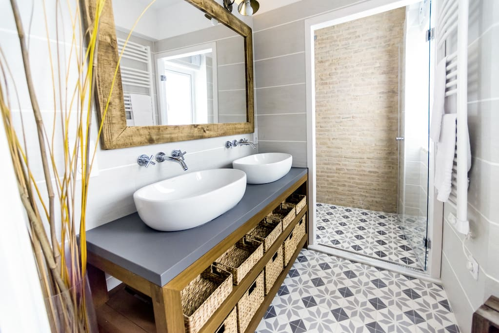 Bathroom with toilet, rain shower, two washbowls and towel heater
