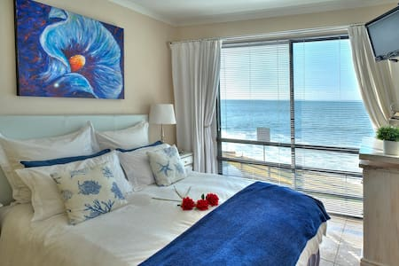 Watch the moonlight on the water and sparkling lights across the bay from your bedroom as waves lap just meters away.
